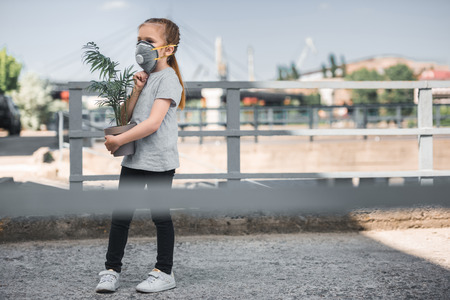 child in protective mask carrying green potted plant, air pollution concept