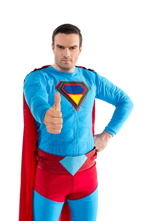 handsome man in superhero costume showing thumb up and looking at camera isolated on white
