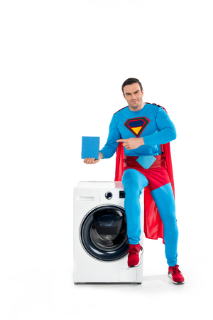 smiling male superhero sitting on washing machine and pointing with finger at soap powder on white
