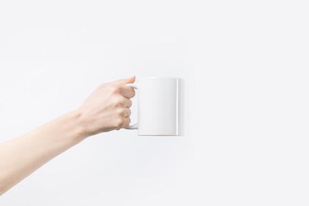 colpo ritagliato della donna che tiene la tazza bianca in mano isolata su bianco Archivio Fotografico