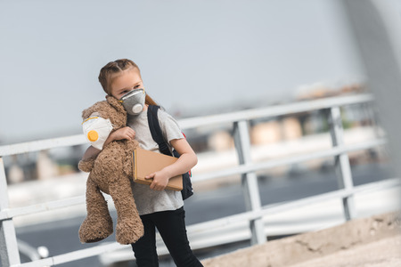 child in protective mask walking with teddy bear and book on bridge, air pollution concept Stock Photo