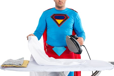 cropped shot of man in superhero costume ironing clothes isolated on white Imagens - 109552958