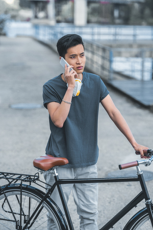 asian teen with protective mask talking by smartphone and leaning on bicycle, air pollution concept