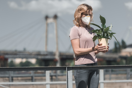 woman in protective mask holding potted plant on street, air pollution concept