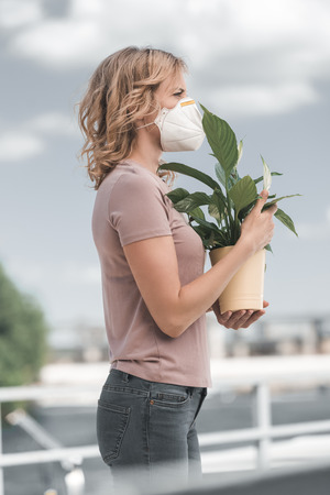 side view of woman in protective mask holding potted plant on bridge, air pollution concept Stock Photo