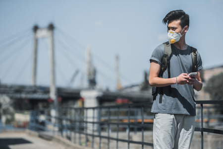 asian teen in protective mask holding smartphone and looking away, air pollution concept