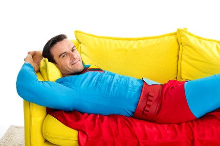 handsome man in superhero costume resting on couch and smiling at camera isolated on white Banco de Imagens