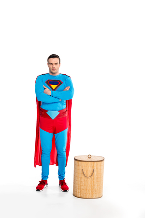 handsome male superhero standing with crossed arms near laundry basket and looking at camera isolated on white Stock Photo