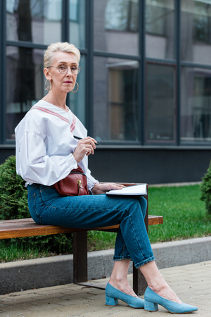 attractive senior woman in stylish outfit writing in diary