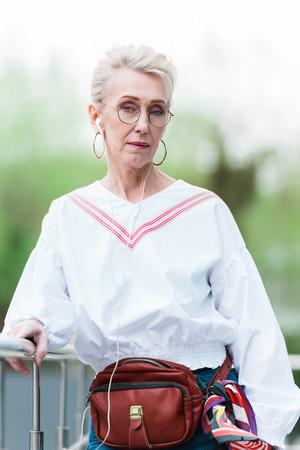 stylish senior woman listening music with earphones Stock Photo