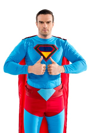 handsome male superhero showing thumbs up and looking at camera isolated on white Banco de Imagens