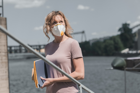 woman in protective mask standing on bridge with documents, air pollution concept Stock Photo