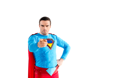 confident male superhero standing with hand on waist and pointing at camera isolated on white Imagens