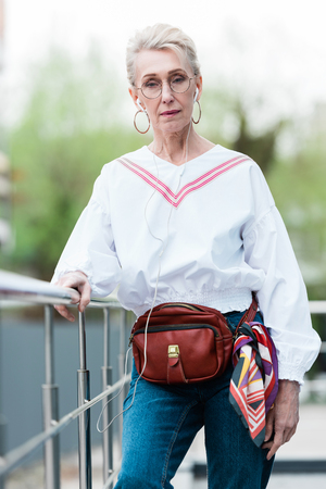 senior woman listening music with earphones and standing near railings