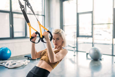 portrait of young caucasian sportswoman training with resistance bands at gym
