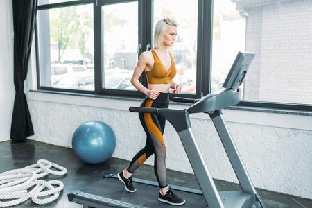 side view of young sportswoman running on treadmill at gym Standard-Bild