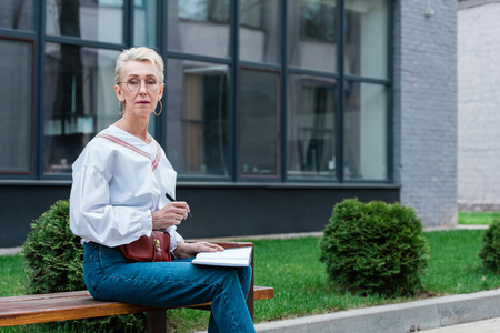 senior woman writing in diary while sitting on bench in park Stock Photo