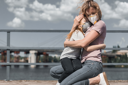mother and daughter in protective masks hugging on bridge, air pollution concept Stock Photo