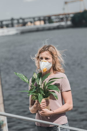 woman in protective mask holding potted plant near river, air pollution concept Stock Photo