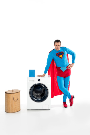 handsome male superhero leaning at washing machine and looking at camera on white Imagens - 109556146