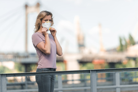 woman wearing protective mask on bridge and looking away, air pollution concept