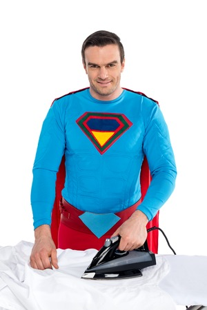 handsome man in superhero costume ironing clothes and smiling at camera isolated on white