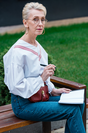 stylish senior woman writing in diary while sitting on bench in park