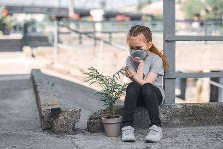 child in protective mask looking at green potted plant, air pollution concept Stock Photo