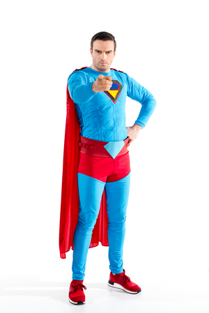 full length view of confident male superhero standing with hand on waist and pointing at camera isolated on white Banco de Imagens