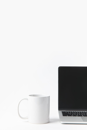 close up view of laptop with blank screen and white mug isolated on white