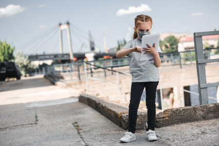 child in protective mask using tablet, air pollution concept