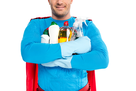 cropped shot of smiling superhero holding cleaning supplies isolated on white Imagens