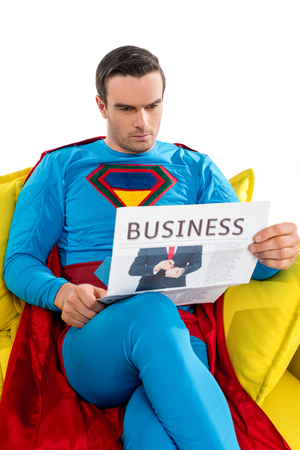 serious male superhero sitting on couch and reading business newspaper isolated on white Imagens - 109555122