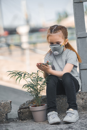 child in protective mask touching green potted plant, air pollution concept