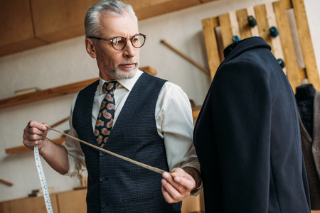 senior tailor holding tape measure and looking at jacket at sewing workshop