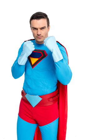 serious male superhero in rubber gloves standing with fighting position and looking at camera isolated on white Imagens