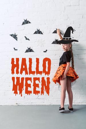 """Vista posterior del niño con falda colgando murciélagos de papel negro en la pared de ladrillo blanco, con letras """"Halloween"""""""