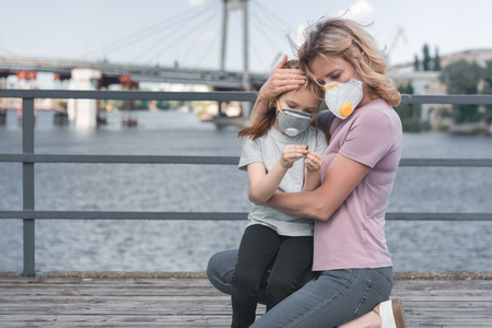 mother in protective mask hugging daughter on bridge, air pollution concept Stock Photo