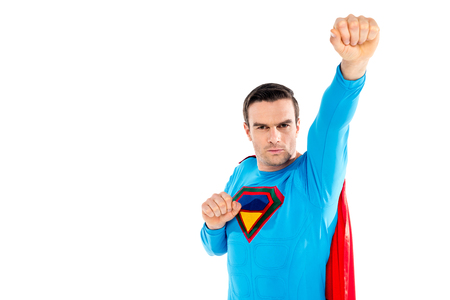 handsome male superhero raising hand and looking at camera isolated on white Banco de Imagens