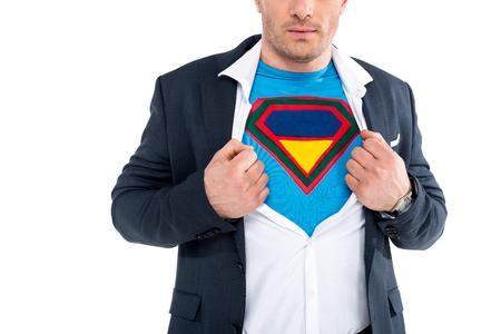 cropped shot of businessman showing superhero costume under suit isolated on white