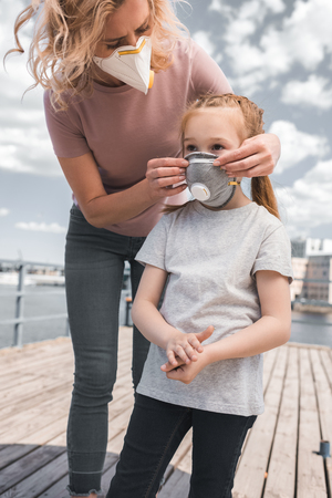 mother wearing protective mask on daughter for breathing, air pollution concept