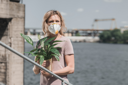 woman in protective mask holding potted plant on bridge, air pollution concept