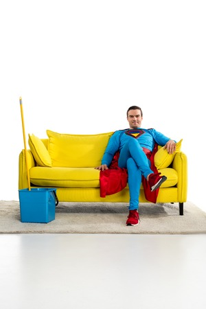 smiling male superhero sitting on couch near bucket and mop on white Imagens