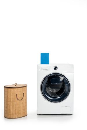 blank box with soap powder on washing machine and laundry basket isolated on white