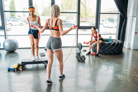 rear view of sportswoman doing exercise with jump rope, african american female athlete exercising on step platform and asian sportswoman doing exercise with dumbbell at gym Reklamní fotografie