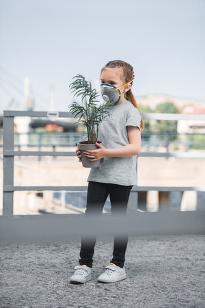child in protective mask holding green potted plant, air pollution concept