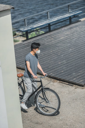 high angle view of asian teen in protective mask standing with bicycle, air pollution concept