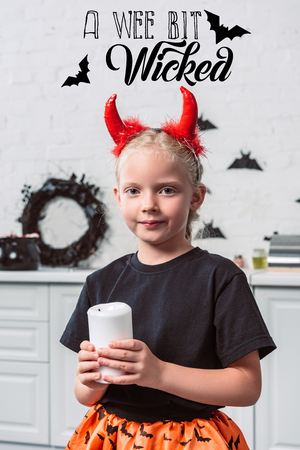 portrait of little kid with red devil horns holding candle in hands at home, halloween holiday concept with a wee bit wicked lettering