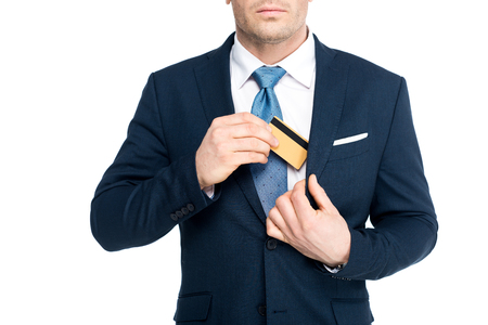 cropped shot of businessman putting credit card in suit jacket pocket isolated on white