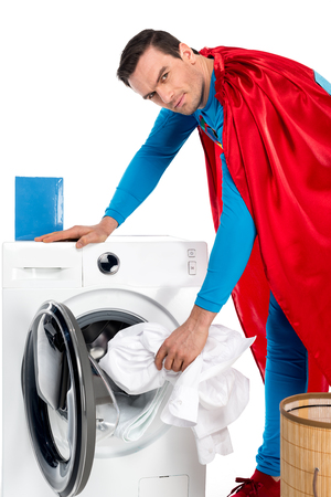 washing clothes in washing machine and looking at camera on white